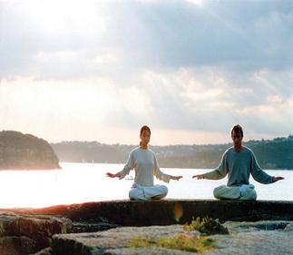 Two people meditating near water