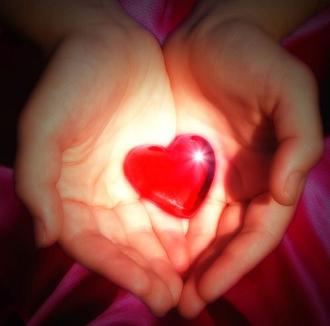 Glowing red heart in hand